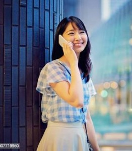 Young japanese woman is talking using her mobile phone